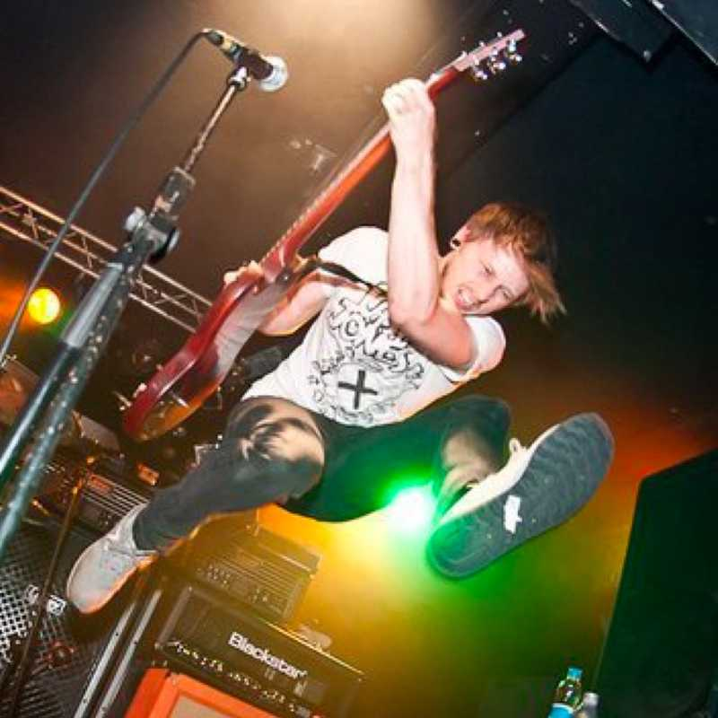 Ross jumping with a guitar at a show